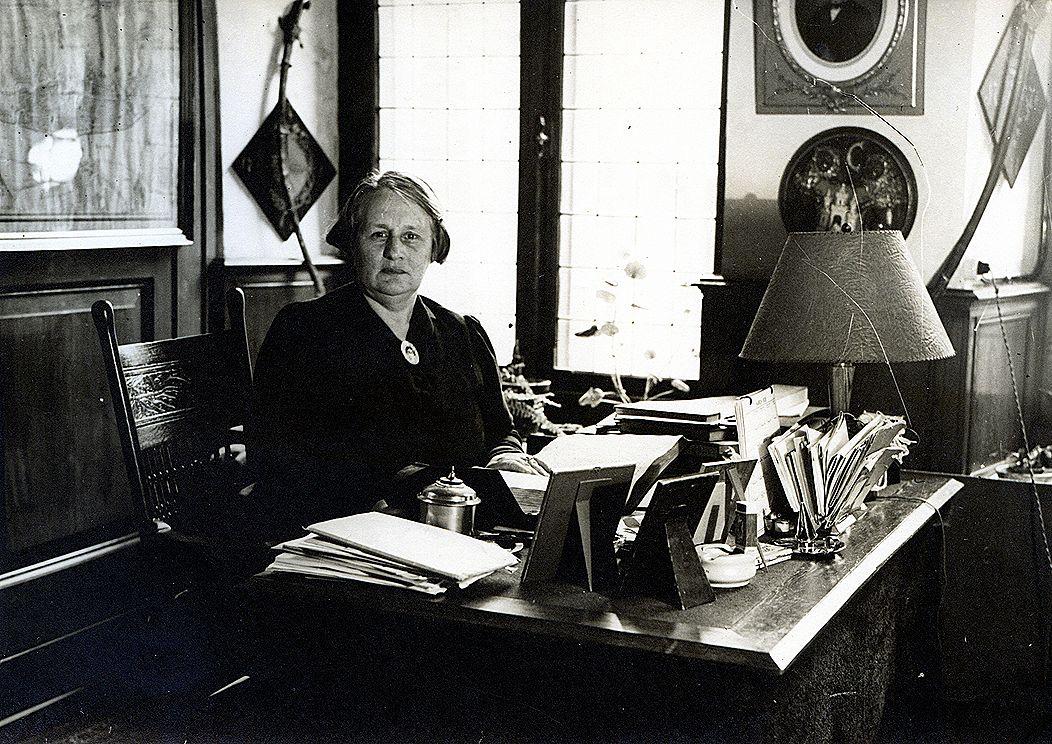 Karakteristieke opname van Clara Welcker in haar werkkamer in wat nu de Gouden Zaal heet in het Stedelijk Museum Kampen ca. 1930. Vanuit het raam had zij zicht op het Gotisch Huis. © Collectie SK, THA, F003198.